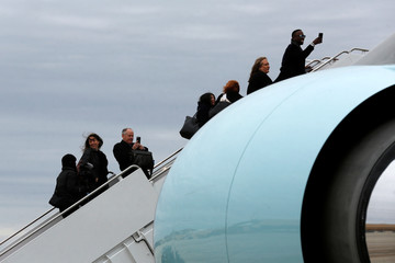 White House staff take pictures as they board Air Force One for Obama's travel to Chicago to deliver a farewell address, from Joint Base Andrews, Maryland