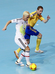 Japan's Morioka fights for the ball against Ukraine's Cheporniuk during their playoff for the quarterfinals of the Futsal World Cup at the Huamark Indoor Stadium in Bangkok