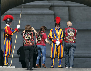 Harley-Davidson bikers pose for a picture beside a Swiss Guard at the Vatican