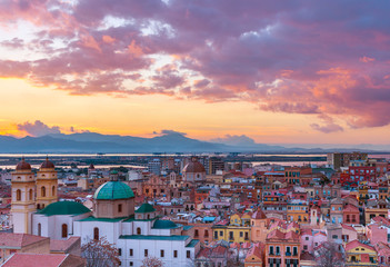 Fototapeten Lavendel Sunset on Cagliari, evening panorama of the old city center in Sardinia Capital, view on The Old Cathedral and colored houses in traditional style, Italy