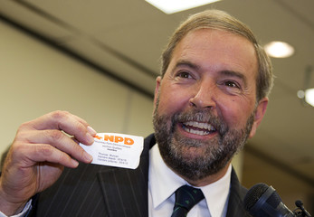 NDP member of parliament Mulcair holds first party membership card as announces his intention to run for party's leadership in Montreal