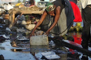 A woman collects water from the ground to clean a table to sell meat in downtown Port-au-Prince