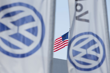 FILE PHOTO - An American flag flies next to a Volkswagen car dealership in San Diego