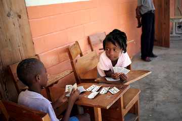 Two kids play cards at the school Inmaculate Conception after Hurricane Matthew in Les Anglais
