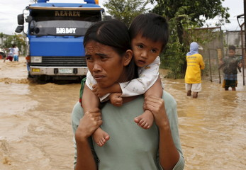 A woman carries her baby on her shoulder as they wade along a flooded highway in Sta Rosa, Nueva Ecija