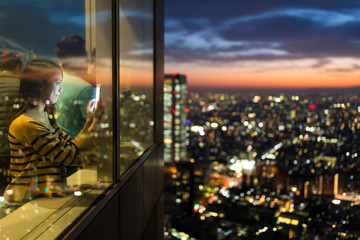 Woman visit the observatory and taking photo of the sunset in Tokyo city