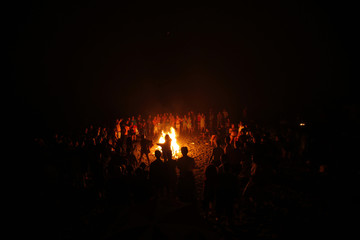 People gather around a bonfire on a beach during the traditional San Juan's night in Malaga