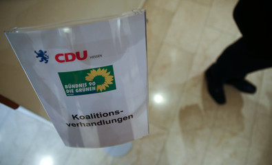 A sign showing the logos of Hesse's conservative Christian Democratic Union (CDU) and green party Buendnis 90/ Gruene shows the way to their coalition talks at a hotel in Wiesbaden