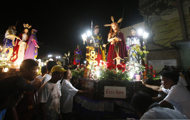 Residents stand near statues of Jesus Christ and other Saints as they take part in a religious procession during Good Friday in Mogpog town