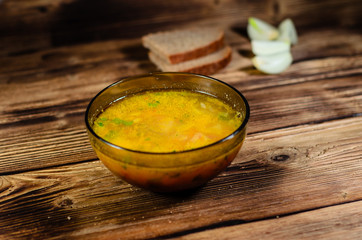 Vegetable soup in a glass bowl on wooden table