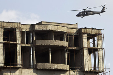 A NATO helicopter flies next to the building which the Taliban insurgents took over during an attack near the U.S. embassy in Kabul