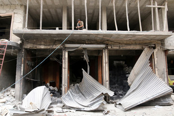 A man stands over damaged shops after airstrikes on the rebel held al-Qaterji neighbourhood of Aleppo