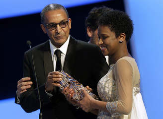 "Director Abderrahmane Sissako and writer Kessen Tall hold their trophy after winning the Best Original Screenplay Award for the film ""Timbuktu"" at the 40th Cesar Awards ceremony in Paris"