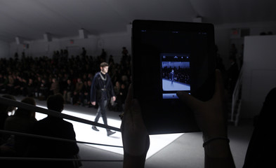 A fashion staff member uses an iPad to tweet live during the Richard Chai Fall/Winter 2012 collection show during New York Fashion Week