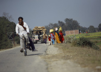 Women are seen balancing their belongings on their heads as they proceed towards the market in Lumbini