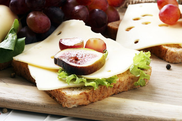 Bread with slices of cheese, some grapes and fig for lunch table. Sharing antipasti on party or summer picnic time