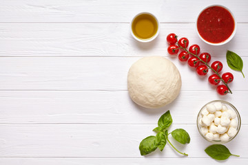 Raw pizza dough with baking pastry ingredients: mozzarella, tomatoes sauce, basil, olive oil, cheese, spices.