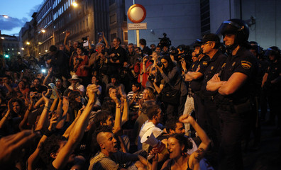 Demonstrators raise their arms in front of Spain's parliament as police stand guard in Madrid
