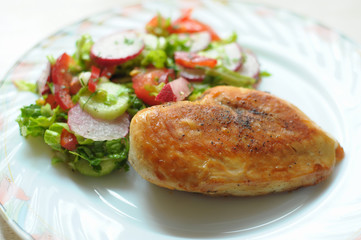 Baked chicken breast with vegetable salad on a white plate