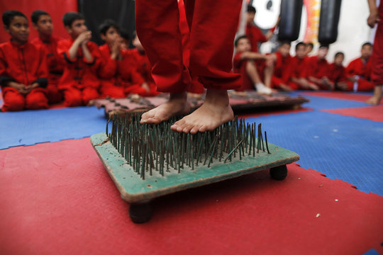 A Palestinian boy stands on a bed of nails during a class at the Red Dragon martial arts club in Beit Lahiya in the northern Gaza Strip