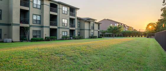 View from grassy backyard of a typical apartment complex building in suburban area at Humble, Texas, US. Sunset with warm light. Panorama style. Wall mural