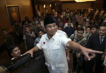 Indonesian presidential candidate Prabowo Subianto gestures after a meeting with members of his coalition in a hotel in Jakarta