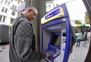A man withdraws cash from an NLB Bank cash machine in Ljubljana