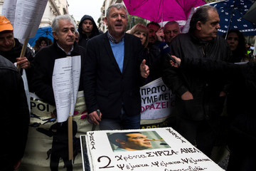 A representative of protesting health workers talks to the media, next to a cake with a picture of Greek Prime Minister Alexis Tsipras as Pinocchio, during a demonstration against government plans affecting the health sector, near the PM's office in Athens