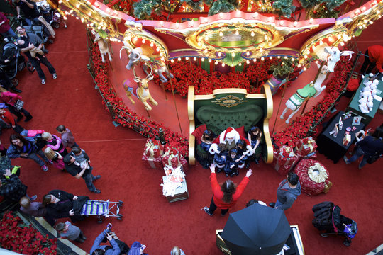 A long line forms to greet Santa Claus, while children are guided to look at the camera as they sit on his lap for a portrait at The Plaza, King of Prussia Mall, in King of Prussia