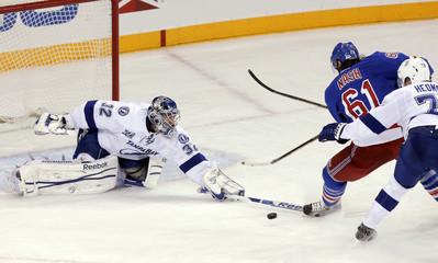 Tampa Bay Lightning goalie Mathieu Garon pokes away a shot by New York Rangers left wing Rick Nash during their NHL game in New York