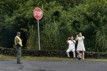 A family takes pictures of Obama's passing motorcade as a police officer blocks traffic at a scenic overlook near Honolulu