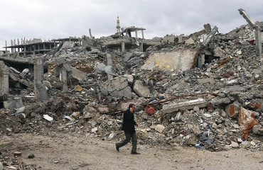 A man walks past damaged buildings in the northern Syrian town of Kobani