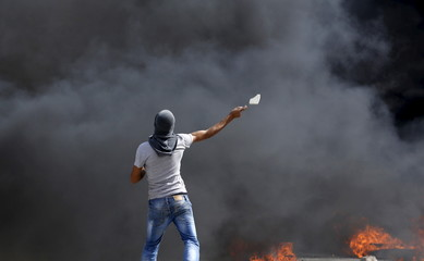 Palestinian throws a stone towards Israeli troops during clashes at Qalandia checkpoint near occupied West Bank city of Ramallah