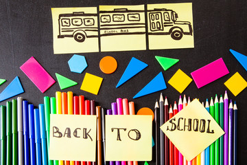 """Back to school background with a lot of colorful felt-tip pens and colorful pencils, titles """"Back to school"""" and drawing of school bus drawn on the yellow pieces of paper"""
