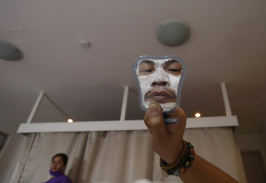 A man wearing a seaweed face mask is reflected in a mirror as he inspects his face at a spa and facial centre in Mandaluyong City, Metro Manila