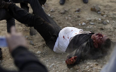 Anti-Mursi protesters hit and drag a Muslim Brotherhood member near the Muslim Brotherhood's national headquarters in Cairo's Moqattam district