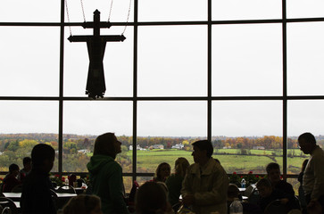 Tourists sit at tables to eat in front of large window and religious symbol inside a gift shop at the Shrine of Our Lady of Martyrs in Auriesville