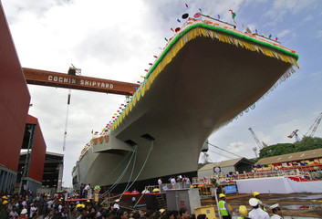"Employees of Cochin Shipyard stand beside India's Indigenous Aircraft Carrier P-71 ""Vikrant"" built for the Indian Navy during its launch in the southern Indian city of Kochi"