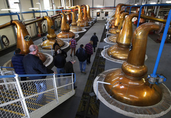 Visitors look at copper whisky stills during a tour of the Glenfiddich whisky distillery in Dufftown, Scotland