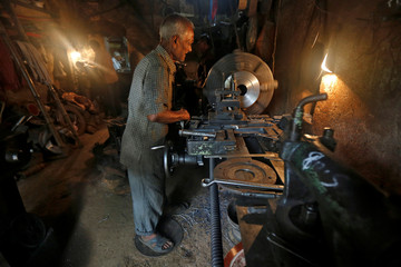 A worker operates a lathe as he makes spare parts of drilling machines at a workshop in Kolkata