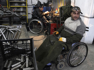 Disabled men work at a wheelchair assembly shop in Tbilisi