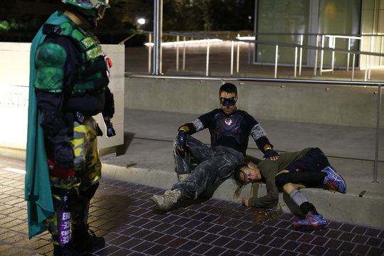 Mr. Xtreme looks on as Fallen Boy comforts a woman in distress during a late night patrol by the Xtreme Justice League in down town San Diego, California