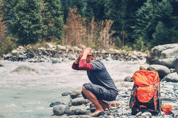 Young man tourist refresh with water in mountain river