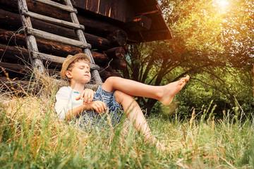 Little lazy boy sleeps under old hayloft in garden