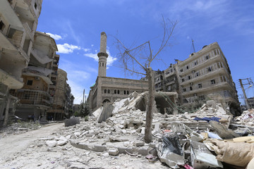 Debris and damage are pictured at a site hit by what activists said was an air strike by forces loyal to Syria's President Assad in al-Shaar neighbourhood of Aleppo