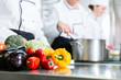chefs preparing meals in commercial kitchen
