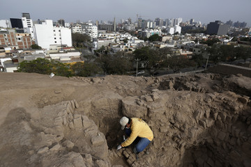 An archaeologist cleans a recently discovered tomb of an intact mummy of the Wari prehispanic culture in Lima