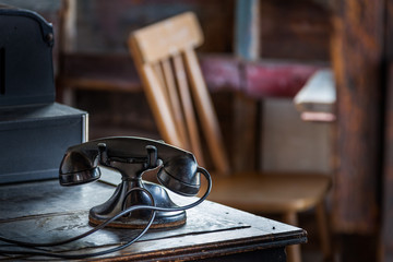Old 1930s telephone on old wooden desk.