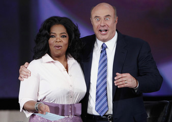 U.S. talk show host Oprah Winfrey smiles as television personality Dr. Phil reacts to seeing himself in a television screen after having his moustache shaved off during a special show in New York City