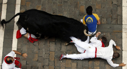 A runner is caught between the horns of an El Pilar fighting bull during the sixth running of the bulls of the San Fermin festival in Pamplona